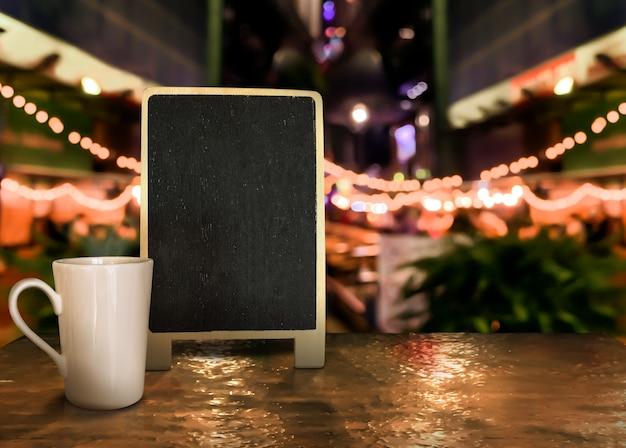 Étiquette en bois de panneau avec une tasse sur la table avec un fond bokeh