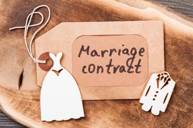 Étiquette brune avec des mots de contrat de mariage. costumes de mariée et de marié en bois à plat.