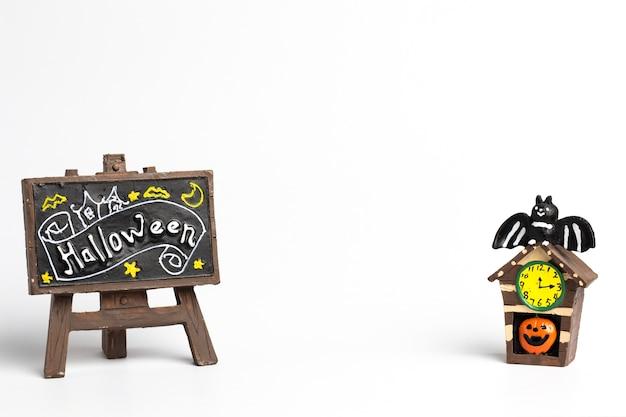 Étiquette brune avec un texte d'halloween et maison d'halloween avec une horloge jaune