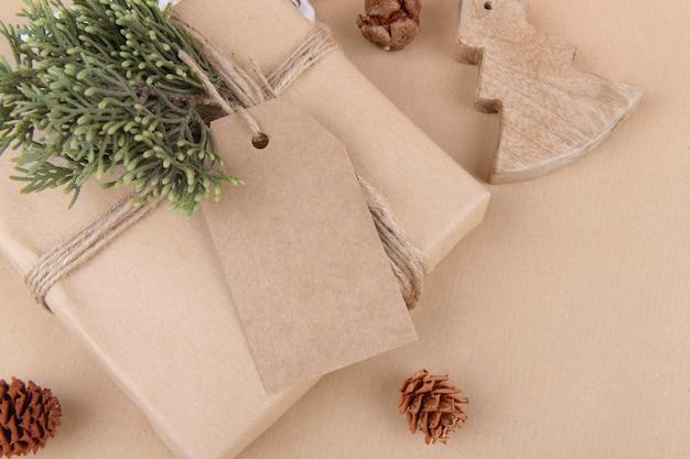 Étiquette-cadeau de noël maquette avec boîte-cadeau enveloppée dans du papier recyclé artisanal avec ruban rouge sur fond blanc