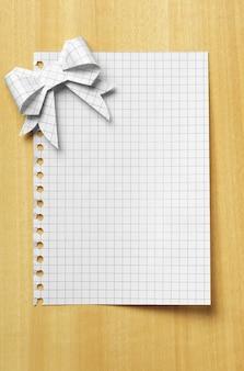 Étiquette-cadeau vierge attachée avec un arc en papier sur une table en bois