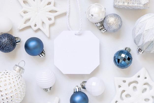 Étiquette-cadeau vierge avec vue de dessus de décorations de noël blanches, bleues et argentées sur une table blanche. composition d'hiver avec maquette de carte d'étiquette vierge, espace de copie