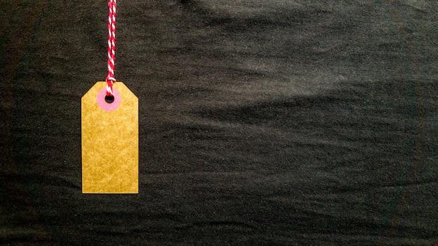 Étiquette en carton marron accrochée à une corde rouge sur fond noir en tissu. copiez l'espace, placez le texte, posez à plat.
