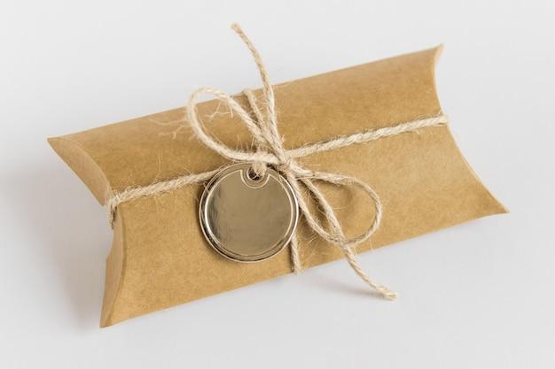 Étiquette dorée métallique et boîte de papier craft avec noeud de filetage brut sur blanc