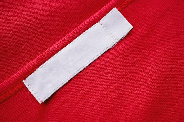 Étiquette d'étiquette de vêtements blancs vierges sur une nouvelle chemise rouge