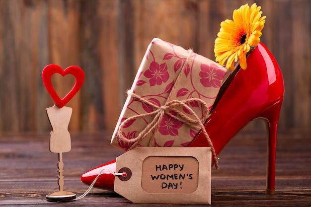 Étiquette et fleur de la journée de la femme. coffret cadeau, chaussure et coeur. exprimez votre appréciation et votre amour. conception d'un beau cadeau.