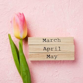 Étiquette de mois de printemps à côté de tulipe