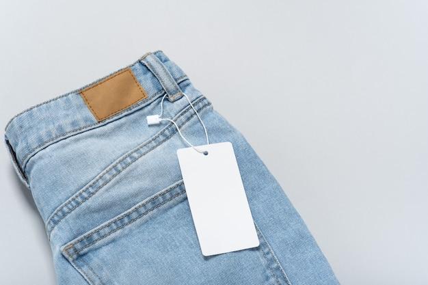Étiquette de papier blanc pour vêtements de jeans, modèle de maquette vierge d'étiquette. fond gris, espace copie, mise à plat