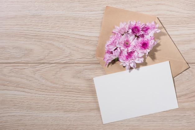 Étiquette en papier blanc vierge avec enveloppe brune et fleurs roses sur table en bois.