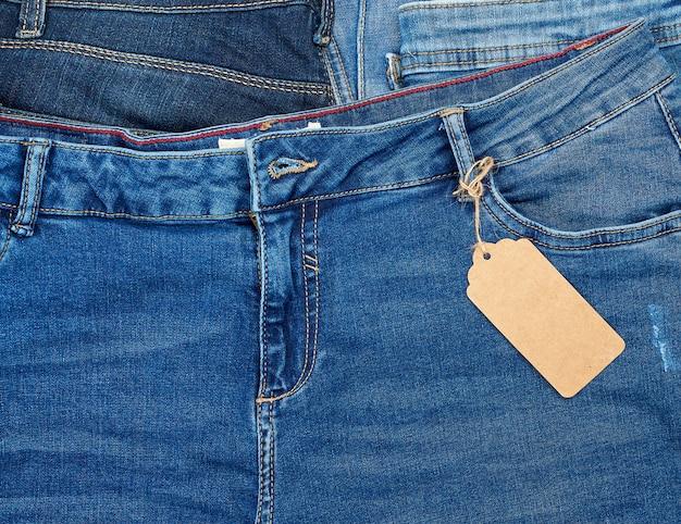 Une étiquette de papier brun rectangulaire vide sur un jean bleu est nouée sur une corde