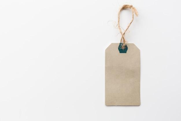 Étiquette en papier avec une corde sur fond blanc
