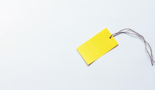 Étiquette en papier jaune sur fond rose blanc, place pour logo, texte, remise ou publicité