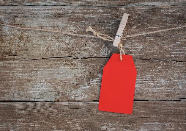 Étiquette en papier rouge vierge tenue sur une pince à linge sur une corde contre un bois rustique