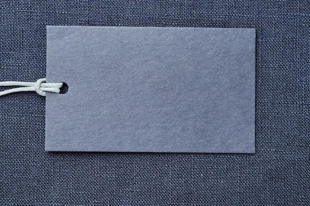 Étiquette en papier vierge ou étiquette de prix sur fond de vêtements en lin bleu