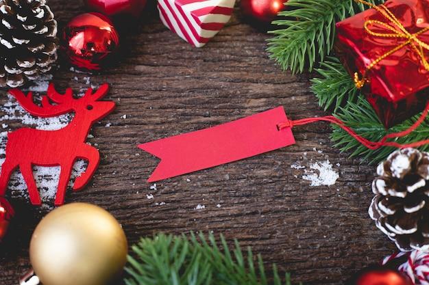 Étiquette rouge vierge avec des décorations de noël sur une table en bois.