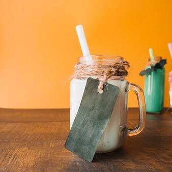 Étiquette sombre sur la tasse avec une boisson de couleur blanche avec de la paille