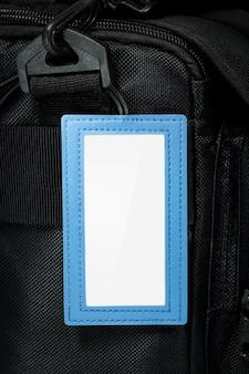 Étiquette suspendue en cuir bleu sur fond de sac de voyage. étiquette de nom vide pour votre conception.