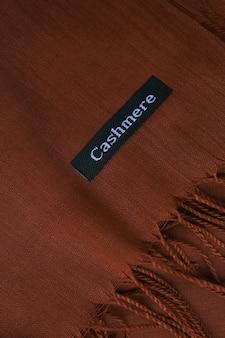 Étiquette de tissu de fond textile chocolat texture cachemire marron foncé sur écharpe en cachemire café mater...