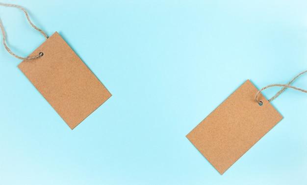 Étiquette de tissu de papier craft vierge ou étiquette sur fond bleu.