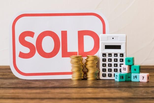 Étiquette vendue, pièces empilées, calculatrice et blocs de maths sur la table en bois
