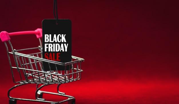 Étiquette de vente du vendredi noir avec chariot de supermarché sur fond rouge foncé