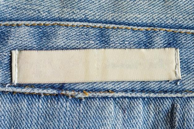 Étiquette de vêtements de soins de blanchisserie blanche vierge sur fond de texture de jeans denim