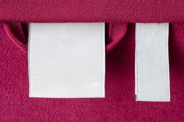 Étiquette de vêtements de soins de blanchisserie blanche vierge sur fond de texture de tissu rouge