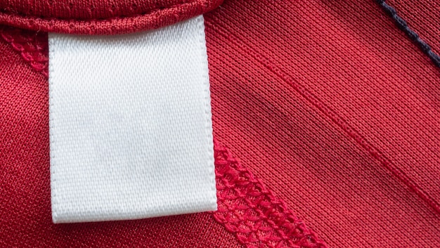 Étiquette de vêtements de soins de blanchisserie vierge blanche sur chemise de sport en polyester rouge
