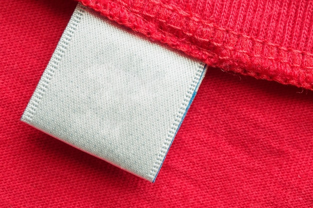 Étiquette de vêtements de soins du linge blanc blanc sur fond de chemise en coton rouge