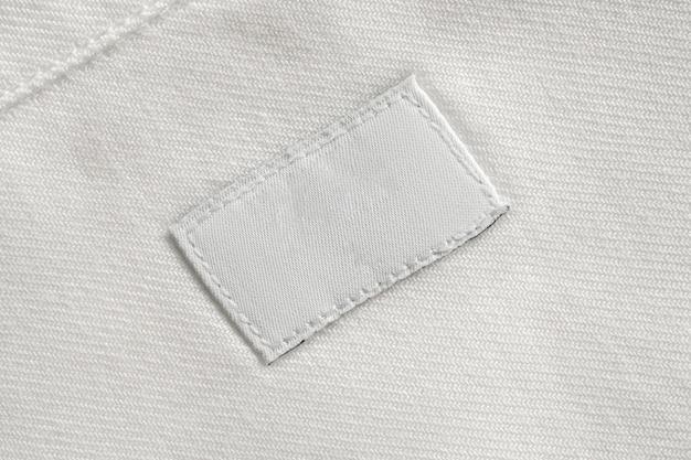 Étiquette de vêtements de soins du linge blanc blanc sur fond de chemise en coton