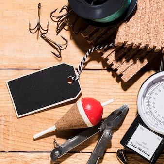 Étiquette vierge; des crochets; flotteur de pêche; pinces; panneau de liège; moulinet de pêche et outil de mesure sur un bureau en bois