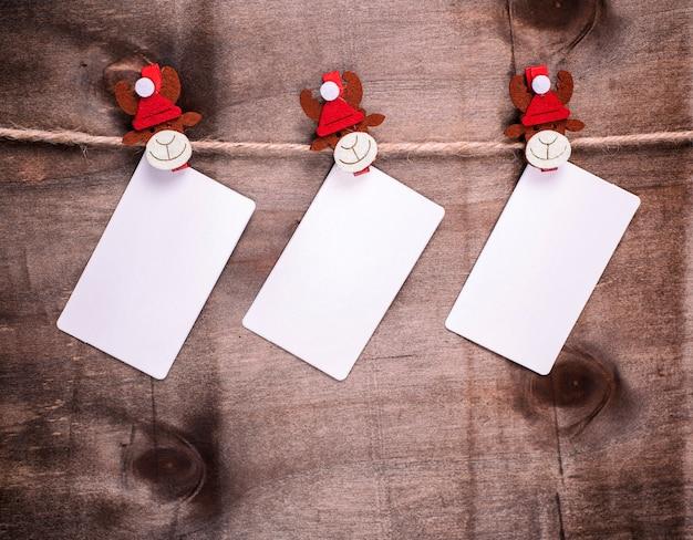 Étiquettes en papier accrochées sur des pinces à linge décoratives