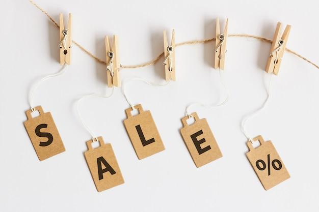 Étiquettes de prix en carton brun avec vente de signe sur blanc