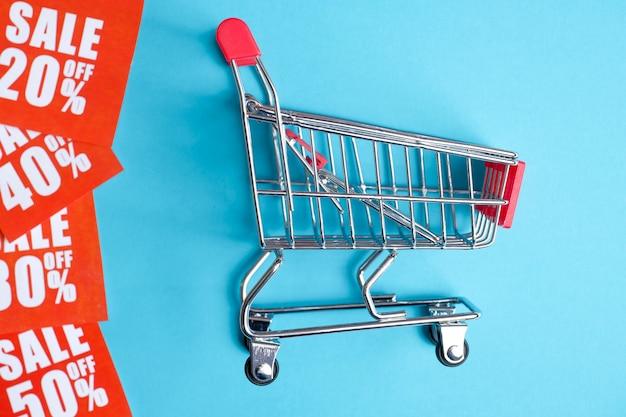 Les étiquettes de vente en différents pourcentages sont imprimées sur du papier rouge à côté du chariot sur un fond bleu.