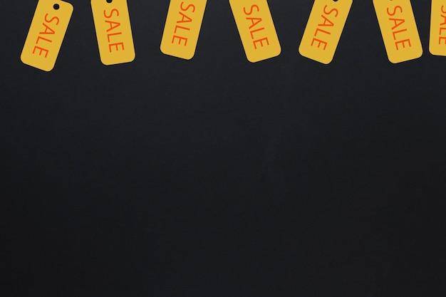 Étiquettes de vente suspendues d'en haut sur fond sombre
