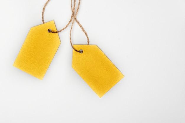 Étiquettes de vêtements jaunes sur fond blanc. modèle de maquette vierge d'étiquettes.