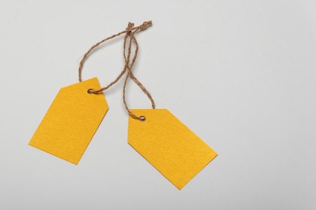Étiquettes de vêtements vierges jaunes sur surface blanche