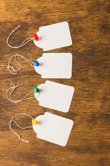 Étiquettes vierges attachées avec des punaises colorées sur une surface en bois texturée