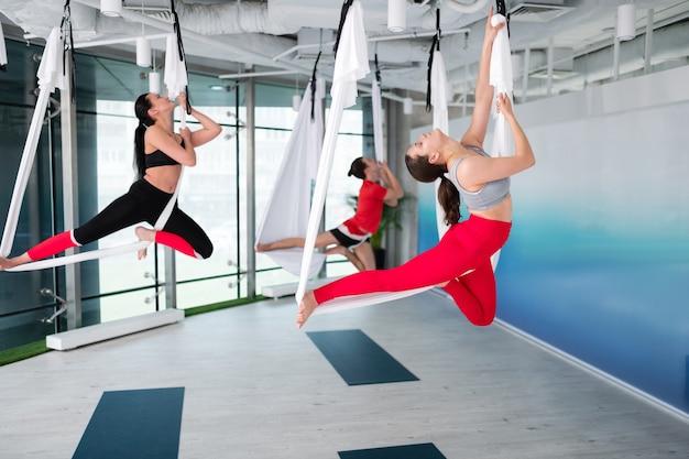 Étirement du dos. deux femmes et hommes en forme active s'étirant le dos tout en essayant le yoga aérien