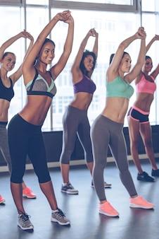 Étirement des filles. jeunes belles femmes gaies avec des corps parfaits en tenue de sport faisant des étirements avec le sourire tout en se tenant devant la fenêtre au gymnase
