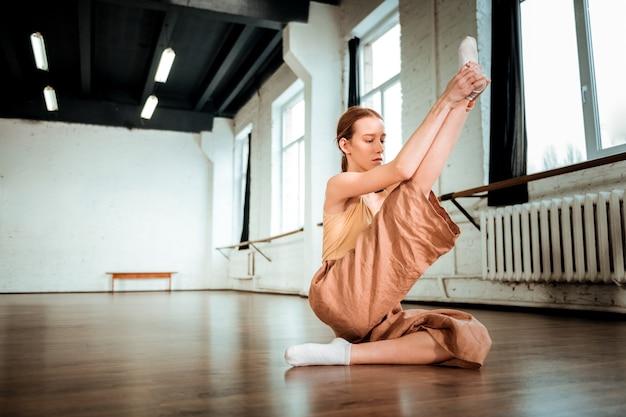 Étirement des jambes. adolescent aux cheveux roux mignon en pantalon orange à la réflexion tout en faisant des jambes étirement