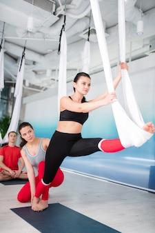Étirement près de l'entraîneur. femme brune assistant à des cours de yoga volant étirant les jambes près de l'entraîneur