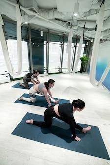 Étirements après le yoga. vue de dessus d'un homme en forme active et de deux femmes qui s'étirent les jambes après le yoga aérien