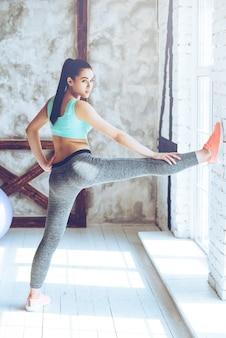 Les étirements la maintiennent forte. belle jeune femme en tenue de sport étendant sa jambe et regardant la caméra tout en se penchant contre le mur au gymnase