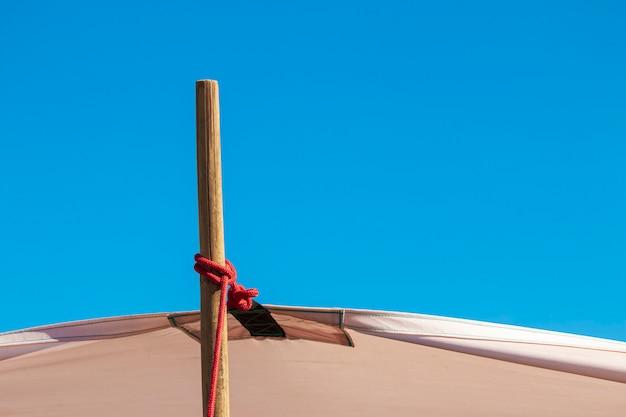 Étirer la toile avec des poteaux en bois sur le ciel bleu
