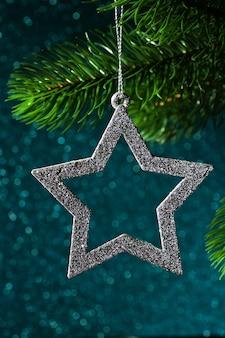 Étoile d'argent sur une branche d'arbre de noël sur un fond bleu brillant de bokeh.