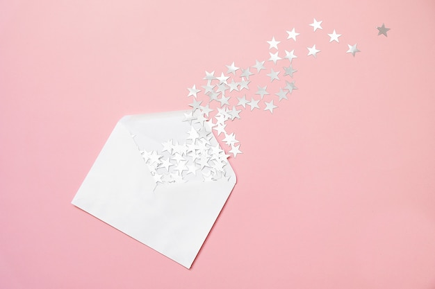 Étoile d'argent saupoudre des confettis dans une enveloppe sur fond rose. noël minimal.