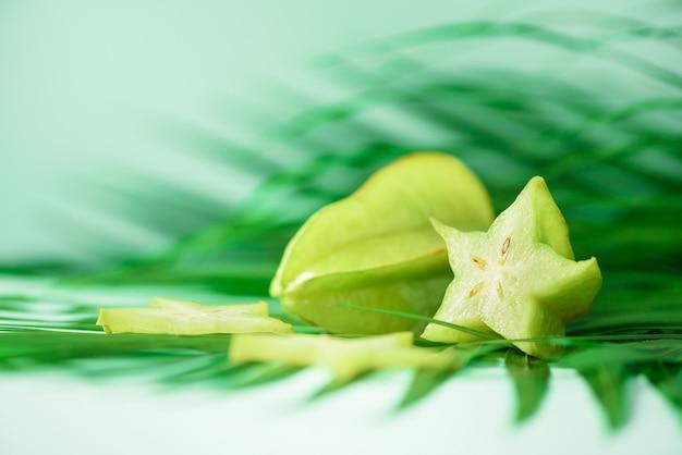 Étoile exotique ou averrhoa carambola sur feuilles de palmier vert tropical