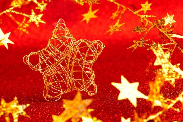 Étoile de fil d'or de noël sur des paillettes rouges