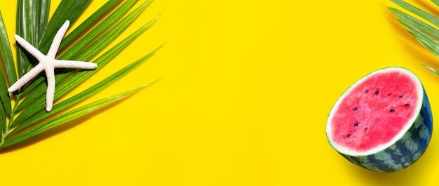 Étoile de mer sur les feuilles de palmiers tropicaux avec pastèque sur fond jaune. profitez du concept de vacances d'été. vue de dessus